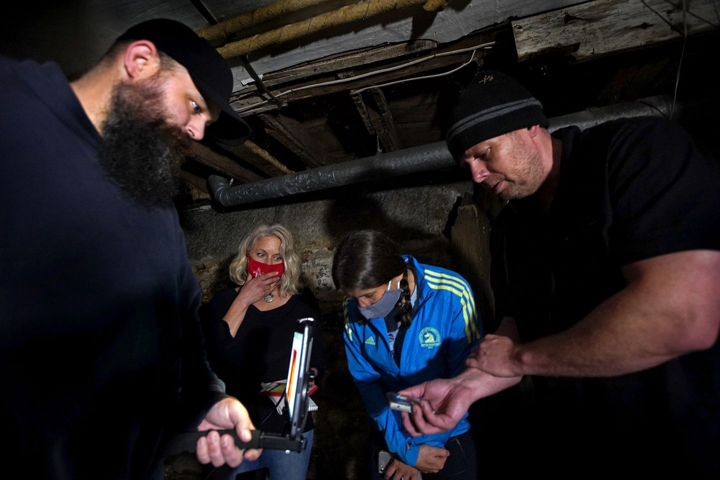 Owner Cory Heinzen and colleague John Huntington try to detect paranormal activity in the cellar of the house with reporter Amanda Milkovits and her sister Susanne Carpenter.