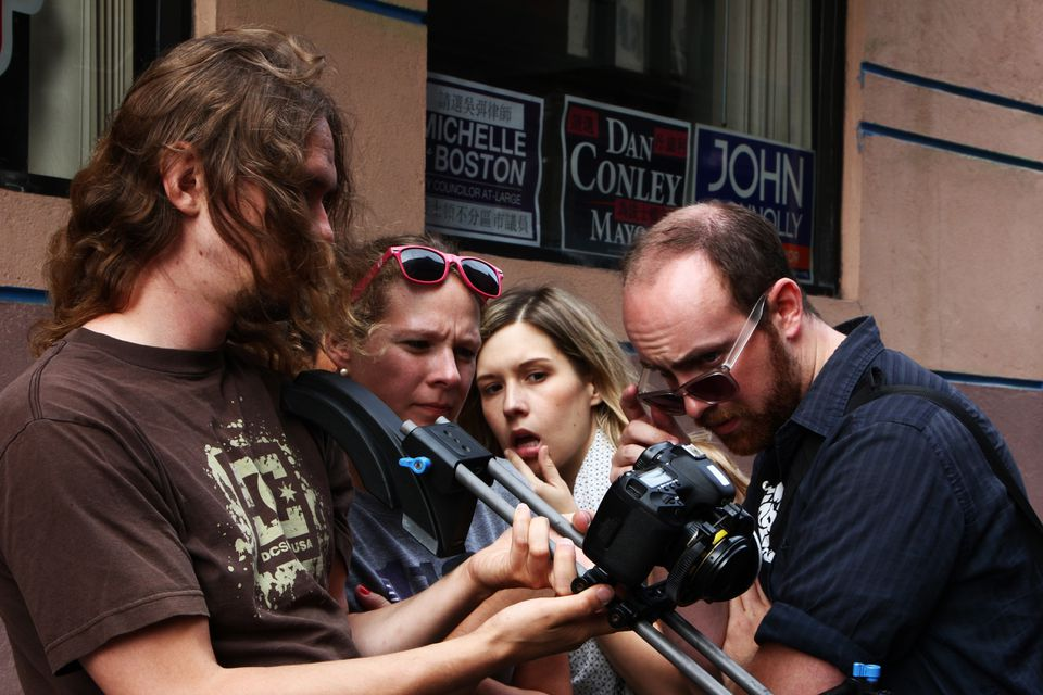"""Web series """"K&A"""" production staff — (from left) Ben Heald,  Katie Shannon, Audrey Claire, and Mike Madden  — watching a playback of a scene they shot in Boston's Chinatown."""