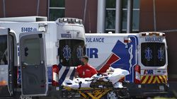 A person is brought to a medical transport vehicle from Banner Desert Medical Center as several transports and ambulances are shown parked outside the emergency room entrance in Mesa, Ariz.