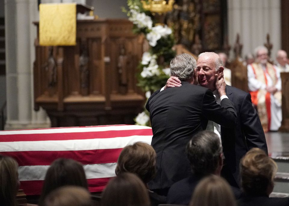 Former President George W. Bush embraced former Secretary of State James Baker (right) after he gave a eulogy .