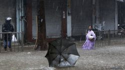 A woman watches her umbrella fly away in the wind during as a powerful cyclone made landfall in Mumbai, India, Monday.