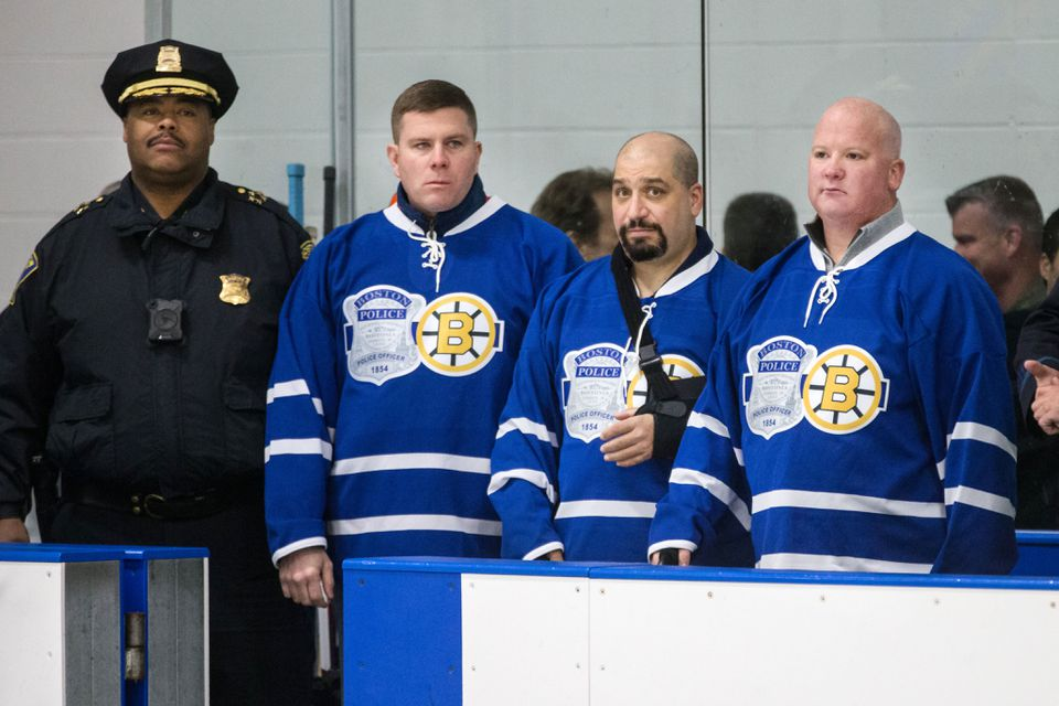 BPD Chief William Gross (left) helped recognize officers Eric Schmidt, Richard Cintolo, and Matt Morris before the start of a game between the Boston Bruins Alumni and Boston Police All Stars.