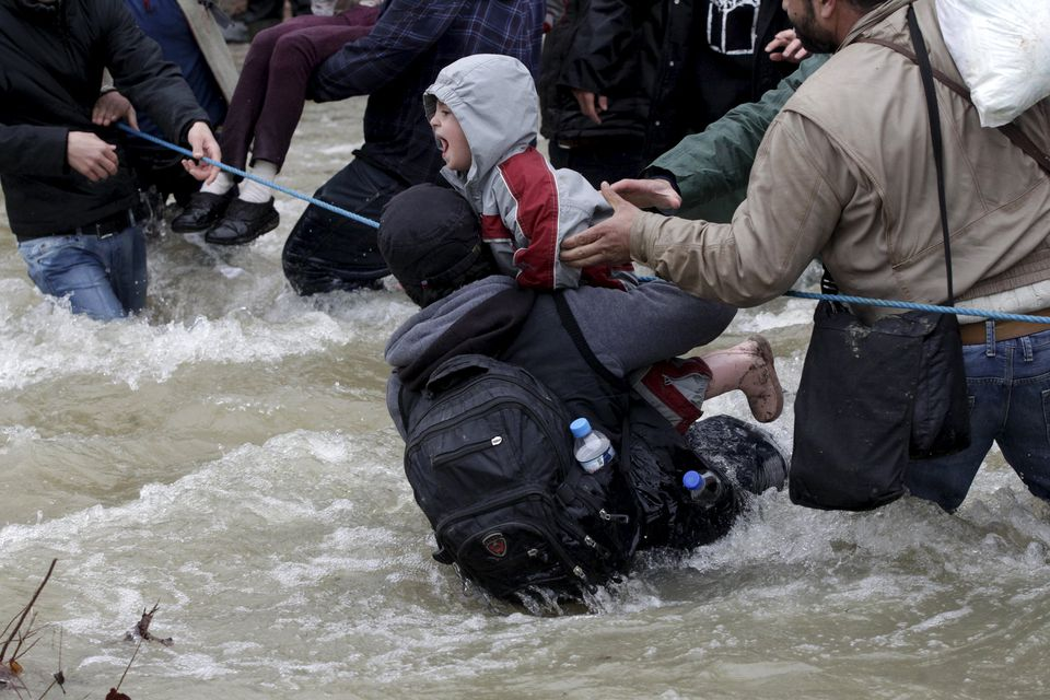 A migrant tried to stop a child from falling in the water as they waded across a river near the Greek-Macedonian border on Monday.