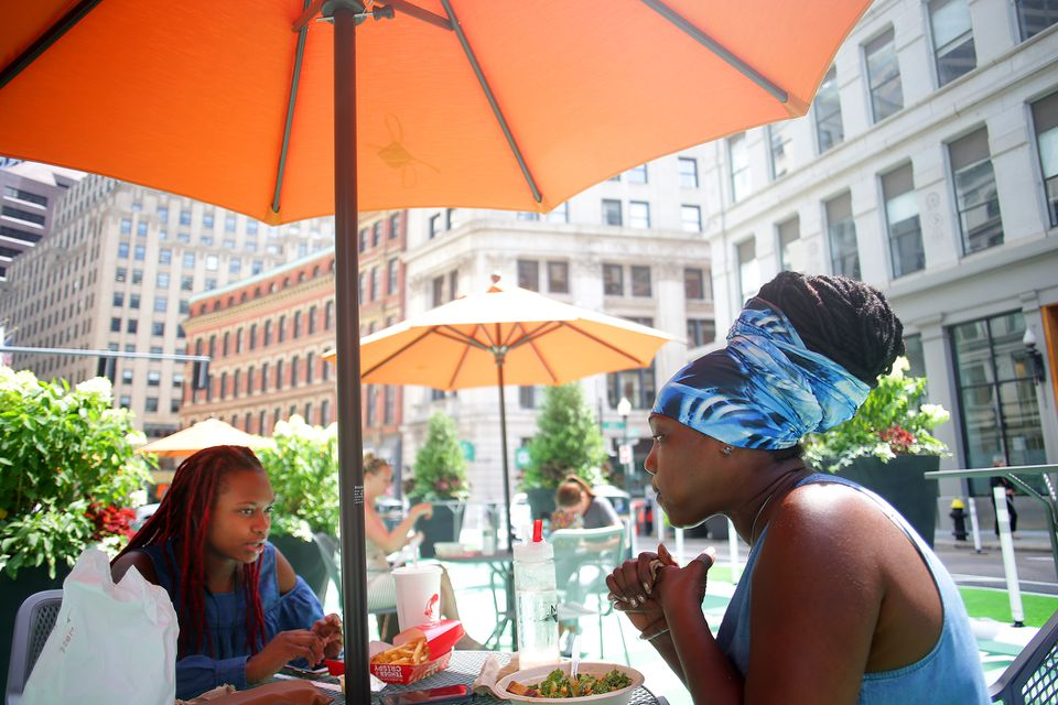 Gail Cummings, right, shared lunch with her daughter Abygail Rudder at a table in the new  plaza at the corner of Franklin and Arch streets.
