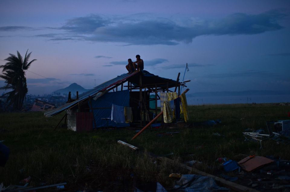 Survivors of Typhoon Haiyan sat atop their newly rebuilt shanty on Sunday in Tacloban, Leyte, Philippines. Some electricity is available to residents in small amounts through diesel generators. There is no running water, but people were receiving water supplied by tankers.