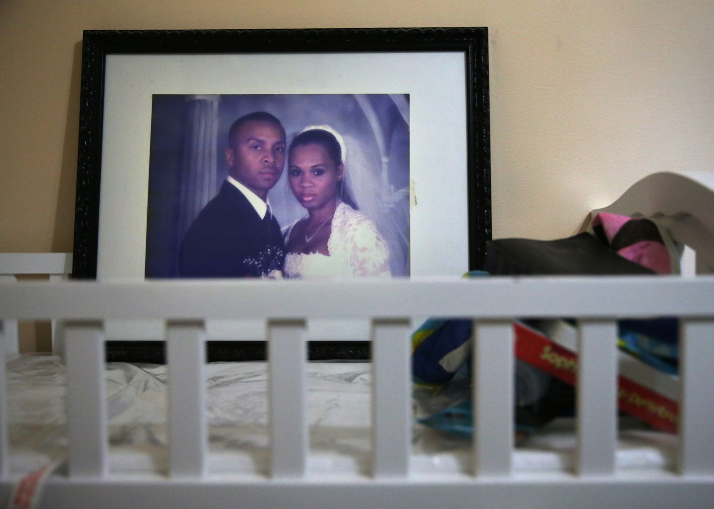 Kenny Fuchu keeps a wedding photograph of himself and his deceased wife, Seveny, on their son's changing table at his home.