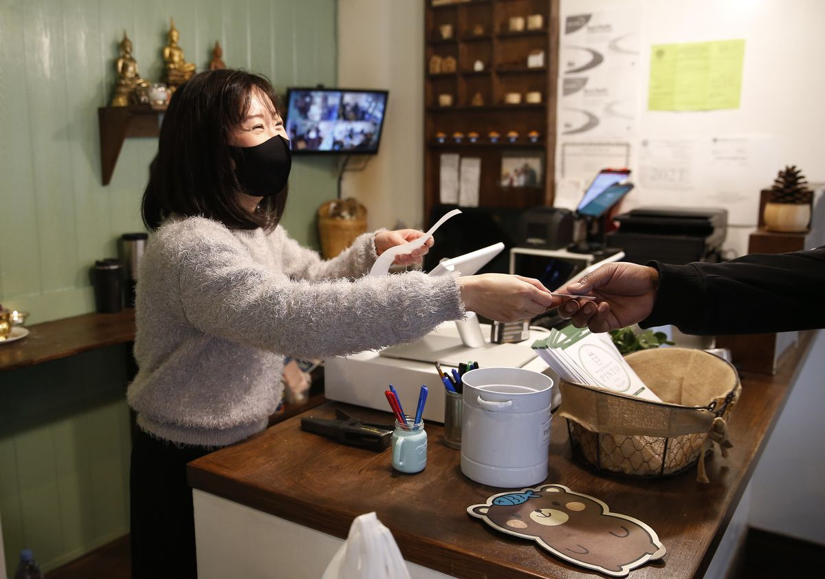 Ching Daranuwat, co-owner of Bangkok Pinto, thanks a customer as she hands him back his credit card.
