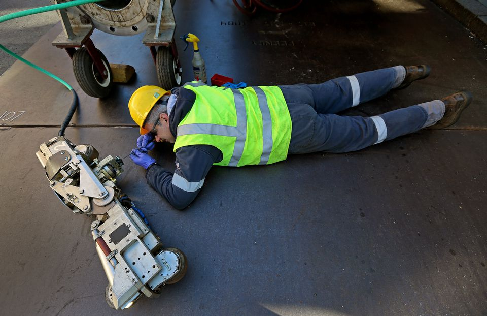 Jay Fabian made adjustments to a robot used repair gas main leaks.