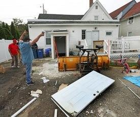 Carlos Morel levanta sus brazos al hablar de la explosión de gas que dañó la casa de su hija en Lawrence el jueves.