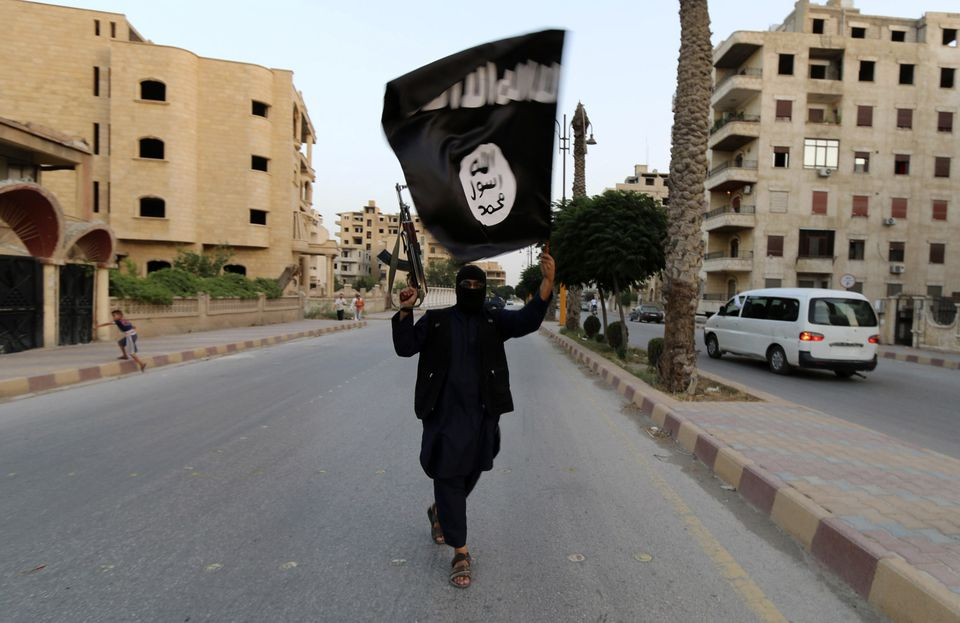 A member loyal to the Islamic State in Iraq and the Levant (ISIL) waved an ISIL flag in 2014.