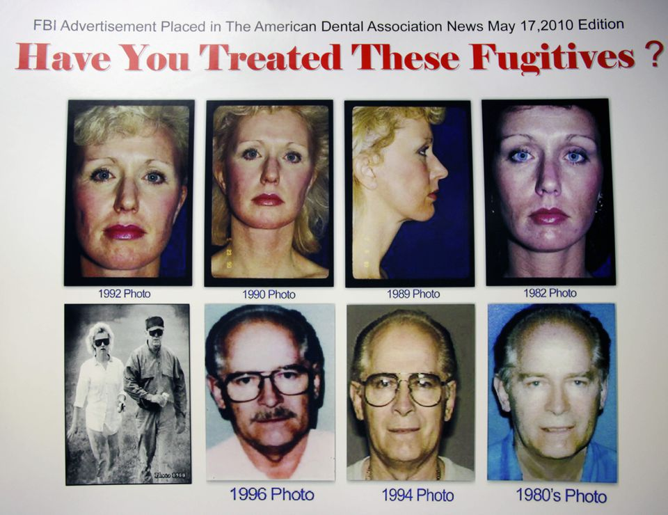 """A poster featuring fugitives James """"Whitey"""" Bulger and Catherine Greig is seen at the FBI field office in Boston, in this June 20, 2011 file photo."""