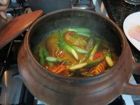 Sudado de pescado y mariscos (fish and seafood stew) cooking in a clay pot.