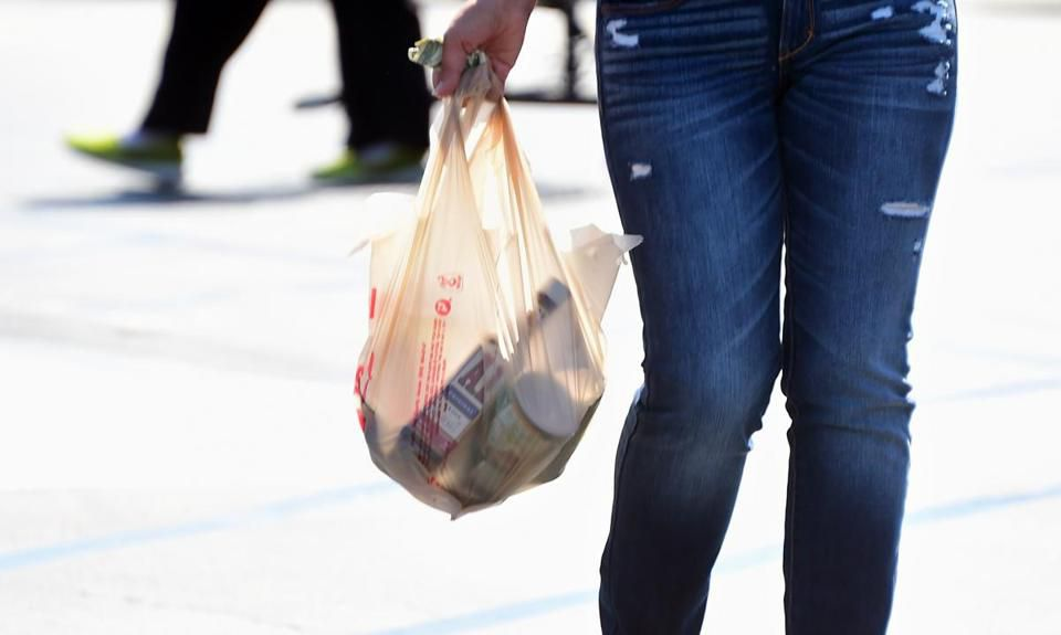 A woman carried her groceries in a plastic bag.